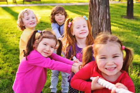 Children play tug of war in the park. Childrens Day, June 1, friendship, childhood, vacation, camp Standard-Bild - 109610042