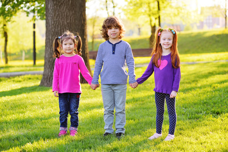 a group of small children smiling holding hands on a background of grass, a tree and a park. Childrens Day, June 1, friendship, childhood. Standard-Bild - 109610051