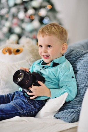 little baby boy with a SLR camera on the background of a Christmas decor Standard-Bild - 109610053