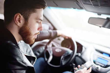 Young cute guy with a beard dials a message on the smartphone in the car Standard-Bild - 109610059