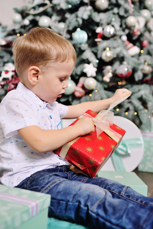 baby boy opens boxes with gifts under the Christmas tree and smiles Standard-Bild - 109610066