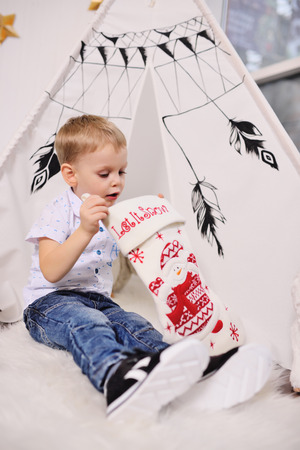 cute little baby boy takes out a present from a Christmas sock against the background of a tent or an Indian wigwam Standard-Bild - 109610069