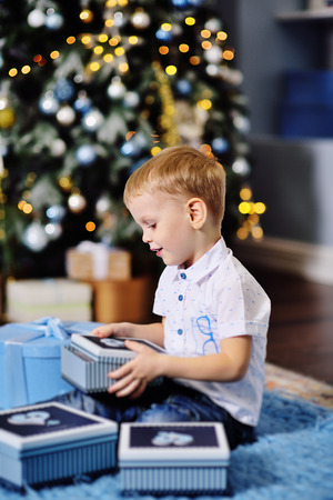 baby boy opens boxes with gifts under the Christmas tree and smiles Standard-Bild - 109610074