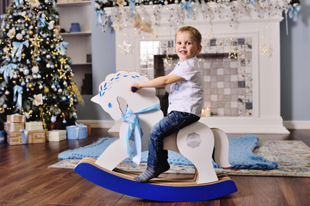 cute baby boy on a toy horse against the background of a Christmas tree Standard-Bild - 109610082