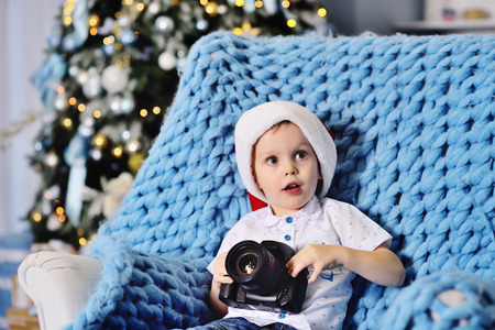 little baby boy with a SLR camera on the background of a Christmas decor Standard-Bild - 109610122