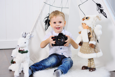 little baby boy with a SLR camera on the background of a Christmas decor Standard-Bild - 109610130
