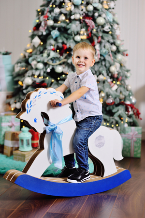 cute baby boy on a toy horse against the background of a Christmas tree Standard-Bild - 109610132