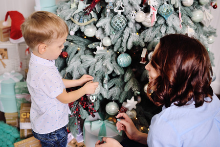 Mom and his young son decorate the tree in a cozy house Standard-Bild - 109610133