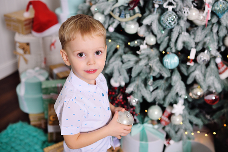 cute baby boy dresses up a christmas tree and smiles Standard-Bild - 109610135