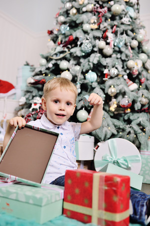 baby boy opens boxes with gifts under the Christmas tree and smiles Standard-Bild - 109610136