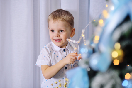 cute baby boy dresses up a christmas tree and smiles Standard-Bild - 109610137