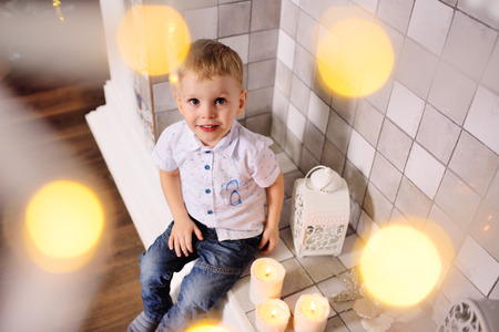 baby boy sitting by the fireplace smiles against the Christmas lights background Standard-Bild - 109610138