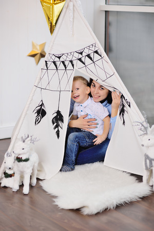 mom and little baby boy hide in a tent or an Indian wigwam and play in the Indians Standard-Bild - 109610139
