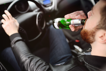 A young handsome bearded man with a bottle of beer or a low-alcohol drink at the wheel of a car. Driving in a state of intoxication Standard-Bild - 109610144