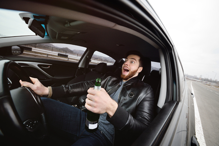 Drunk young man with a beard with a bottle of beer in his hand behind the wheel of a car. Emergency situation, violation of law, drunk driving Standard-Bild - 109610146