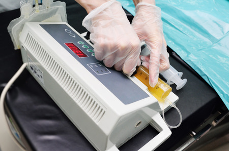 syringe with plasma in a special medical device during surgery