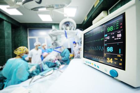 un grupo de cirujanos opera en primer plano del monitor de funciones vitales del paciente.