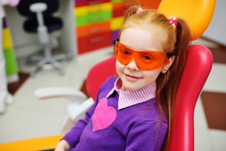 baby girl in dental glasses smiling sitting in dental chair. Pediatric dentistry Imagens