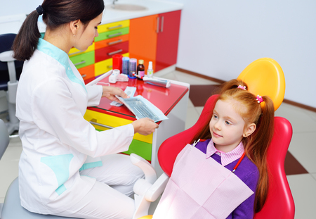 childrens dentist examines the teeth and mouth of the child - a cute red-haired girl sitting in a dental chair. Pediatric dentistry