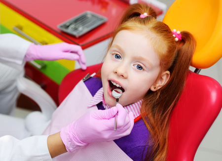 little girl smiling in red dental chair. The dentist examines the teeth of the childs patient. Pediatric dentistry