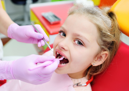 the child is a sweet little girl without front milk teeth in the dental chair. The dentist examines the teeth of the childs patient. Pediatric dentistry