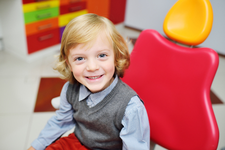 portrait of a smiling child with blonde curly hair on examination in a dental chair. Pediatric dentistry Imagens