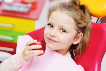 baby girl sitting in a red dental chair smiling with a red Apple in her hands. Pediatric dentistry, milk teeth. Imagens