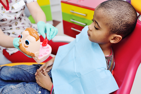 a pediatric dentist teaches an African American child who sits in a dental chair to brush his teeth properly. Pediatric dentistry