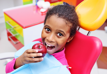 cute black African American girl child smiling and eating a ripe red Apple sitting in a red dental chair at the examination at the childrens dentist.