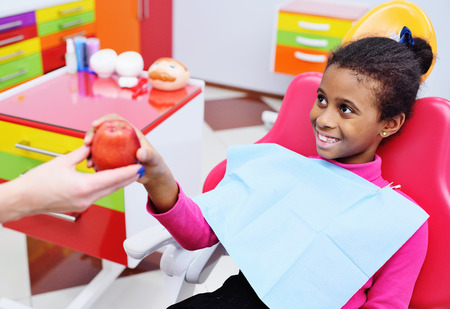 baby dentist gives a ripe red Apple to a little black African American girl in a dental chair. Imagens