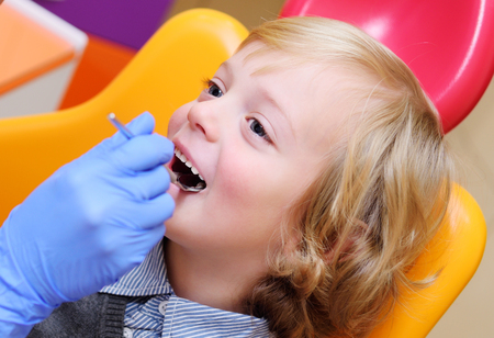 smiling baby boy with blond curly hair in dental chair. Pediatric dentistry.