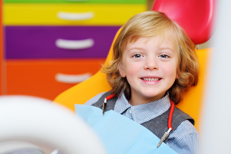portrait of a smiling child with blonde curly hair on examination in a dental chair. Pediatric dentistry Фото со стока