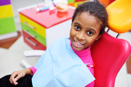 cute black baby girl smiling sitting in a red dental chair at the examination at the childrens dentist Zdjęcie Seryjne