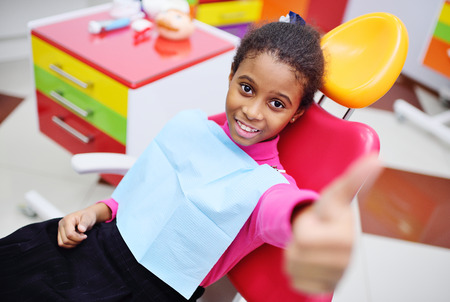 cute black baby girl smiling sitting in a red dental chair at the examination at the childrens dentist Фото со стока