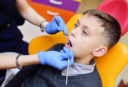 young woman dentist examines the teeth of a baby boy sitting in the dental chair. Pediatric dentistry
