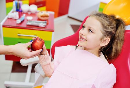 dentist gives ripe red Apple baby girl in the dental chair. Pediatric dentistry Zdjęcie Seryjne