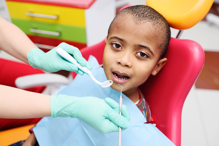cute black baby boy African American smiling sitting in the dental chair at the examination at the childrens dentist.