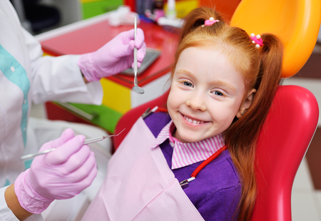 the child is a little red-haired girl smiling sitting in a dental chair. Pediatric dentistry, baby teeth