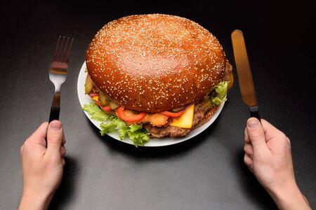 Enorme hamburguesa gigante en un primer plano de fondo oscuro
