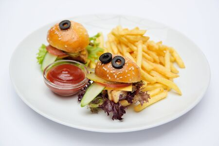 Funny baby burgers on a plate close-up with French fries and sauce