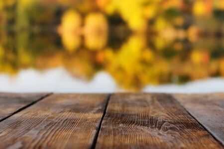 wooden background on the background of autumn forest and lake or river in the blur. Autumn concept. Space for text, copy space, design preset. Zdjęcie Seryjne