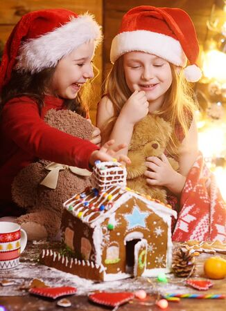 two cute funny little girls in red Santa hats covered with a plaid smile against the background of Christmas decor and lights and make a beautiful gingerbread house Фото со стока