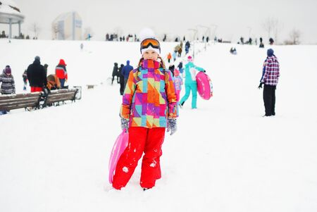 little girl in colored outerwear with a sledge child carriers in hands on the background of snow slope. Winter entertainment
