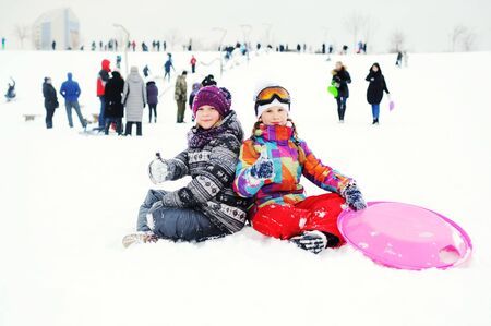 two little girl friends in winter outerwear sitting on the snow with a sled plate in his hands smiling against the background of the snow slope. Winter entertainment