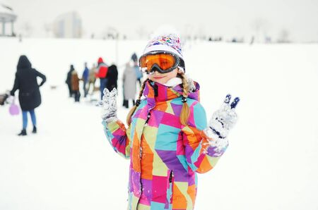 a little girl in a colored ski suit and snowboard glasses on the background of a snowy slope and people in a ski resort