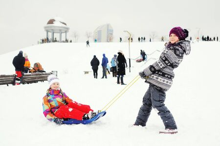 a little girl sledding her friend on the background of people and snow slope. Winter entertainment