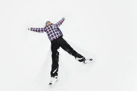 a young man in a plaid outerwear or jacket lies on the snow and makes the figure of an angel. Winter fun Фото со стока