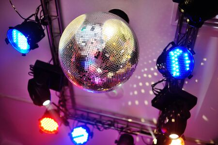 disco ball and colored spotlights in a night club. Party, light music , night life.