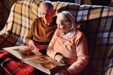 two elderly people-a man and a woman looking at a family photo album smile and hug each other wrapped in a warm plaid blanket.
