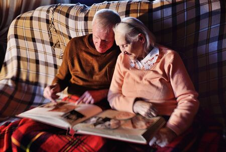 an elderly married couple-a man and a woman in a cozy house sitting on the sofa and wrapped in a warm plaid plaid hug each other and smile while viewing the family photo album.